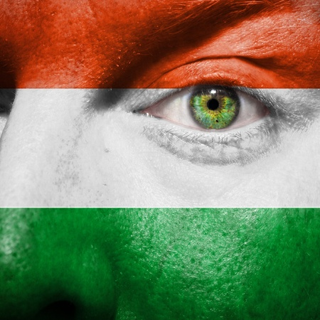 Flag painted on face with green eye to show hungary support photo
