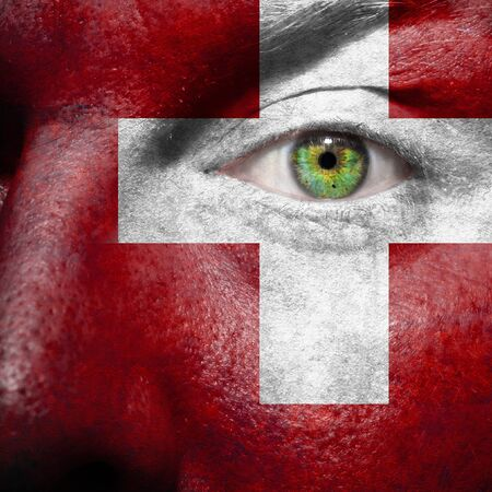 switzerland flag: Flag painted on face with green eye to show Switzerland support