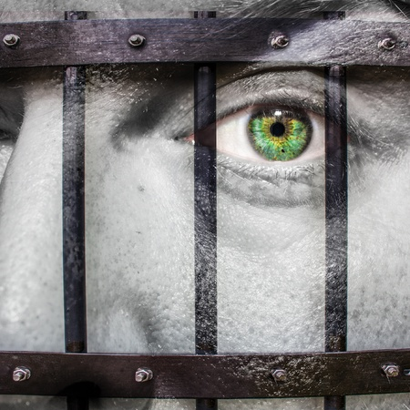locked up: Face with green eye and painted prision
