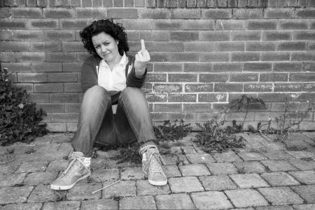 hands off: Mujer joven que muestra el dedo medio en blanco y negro