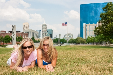 Two woman friends lying on the grass Stock Photo - 13980043