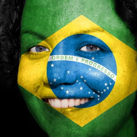 ブラジルのサポートを示すスポーツの彼女の顔に描かれた旗を持つ女性