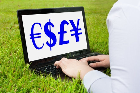 Woman working outdoors on laptop showing currency photo