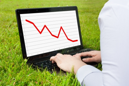 Woman working outdoors on laptop showing downward line graph photo