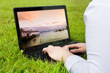 holiday destination: Woman searching holiday destination outdoors on laptop Stock Photo