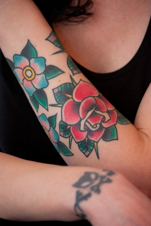 Tattoo of flower and rose on female arm photo