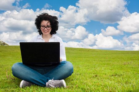 lunchbreak: Woman working outdoors in a meadow sitting up with a laptop