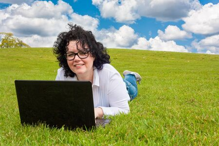 lunchbreak: Woman working outdoors in a meadow and looking up from laptop