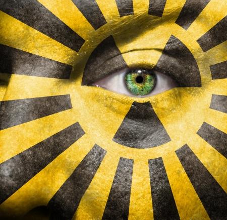 放射性標識と x 線写真に描かれた、核保有議論についての意識を高めるために顔をマン