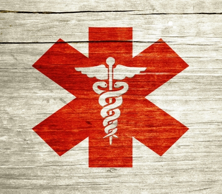 Red Caduceus on wood with grunge design 写真素材