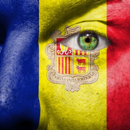 chad: Flag painted on face with green eye to show Andorra support Stock Photo