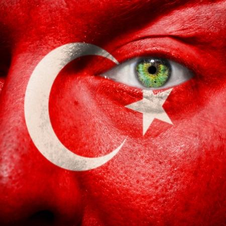 Vlajka namaloval na obličej se zeleným okem ukázat podporu Turecko Reklamní fotografie