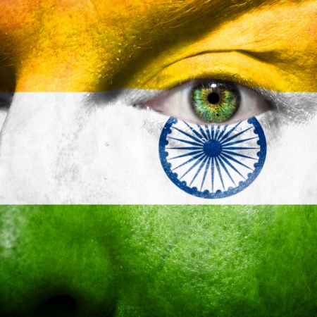 Flag painted on face with green eye to show india support Stock Photo