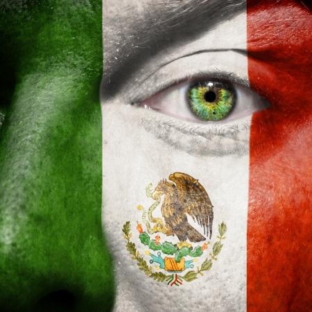 メキシコのサポートを示す緑色の目と顔に描かれた旗