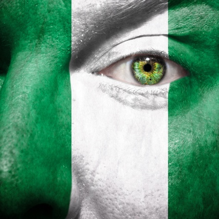 country nigeria: Flag painted on face with green eye to show nigeria support Stock Photo