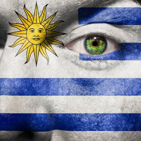 bandera de uruguay: Bandera pintada en el rostro con los ojos de color verde para mostrar su apoyo Uruguay Foto de archivo