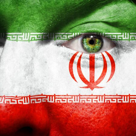 Flag painted on face with green eye to show Iran support photo