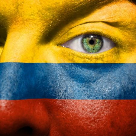 la bandera de colombia: Bandera pintada en el rostro con los ojos de color verde para mostrar el apoyo de Columbia