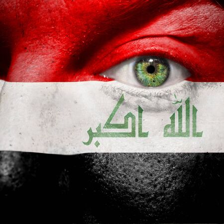 Flag painted on face with green eye to show Iraq support photo