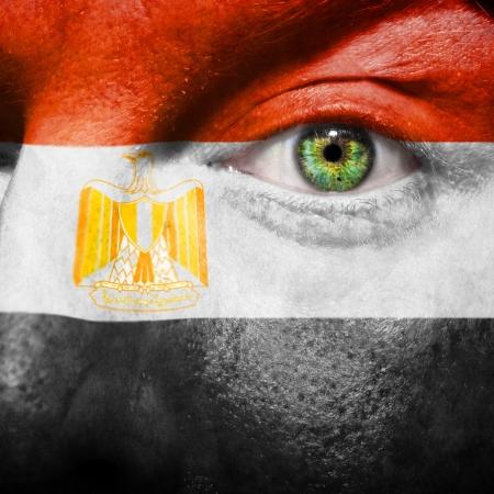flag of egypt: Bandera pintada en el rostro con los ojos de color verde para mostrar el apoyo de Egipto Foto de archivo