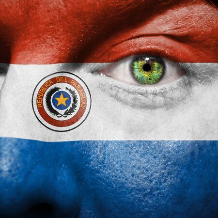 Flag painted on face with green eye to show Paraguay support photo