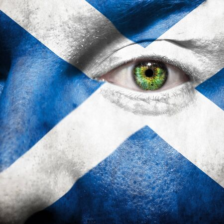 face paint: Flag painted on face with green eye to show Scotland support Stock Photo
