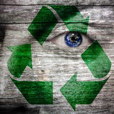Recycling symbol painted on face and earth as eye to create awarenss for a green earth photo