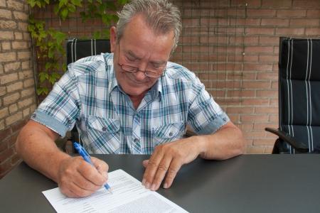 Charmante mannelijke senior burger met een glimlach op zijn gezicht tekenen van een juridisch document in zijn achtertuin