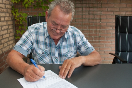 the signature: Charming male senior citizen with a smile on his face signing a legal document in his backyard