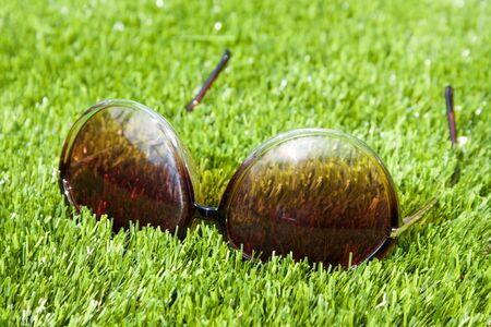 Sunglasses lying on artificial grass or turf with brown gradient glasses photo