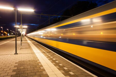 speeding: Yellow and blue train leaving a small roofless dutch train station at night in the Netherlands