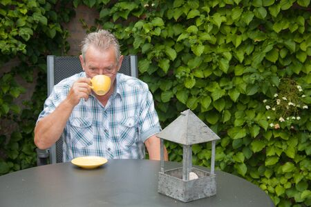 Retired senior Dutch man drinking a cup of hot coffee in his back yard Stock Photo - 14731394