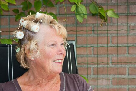 Senior woman smiling and wearing hair rollers or hair curlers sitting in her backyard Stock Photo - 14731401