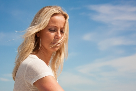 Young beautiful woman in deep thoughts against a blue peaceful sky Stock Photo - 14731371