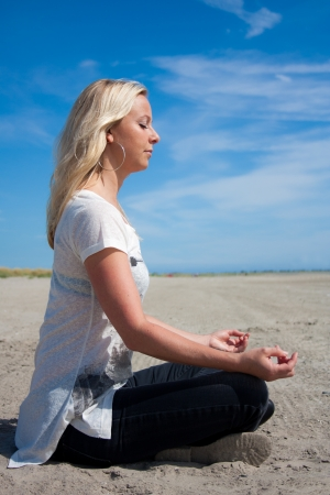 Young beautiful woman sitting in Lotus position on the beach meditating or performing yoga photographed from the side Stock Photo - 14731378