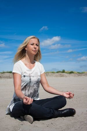 Young beautiful woman sitting in Lotus position on the beach meditating or performing yoga Stock Photo - 14731377