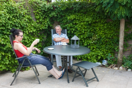 Dutch Daughter and Father sitting at a garden set in the back yard chatting and drinking a hot beverage photo