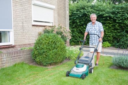 Nederlandse senior glimlachend en het maaien van zijn voortuin gras met een elektrische maaier als vrije tijd activiteit na pensioen Stockfoto
