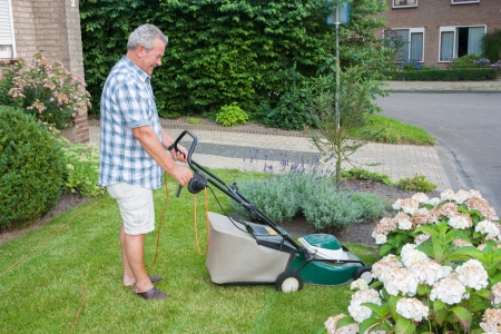 Dutch senior smiling and mowing his front yard grass with an electric mower as spare time activity after retirement photo