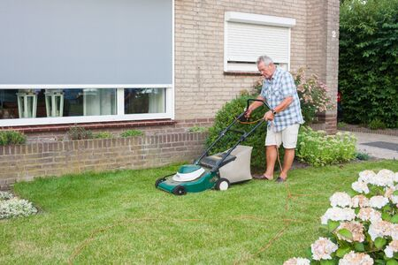 Dutch senior with serious look and mowing his front yard grass with an electric mower as spare time activity after retirement photo