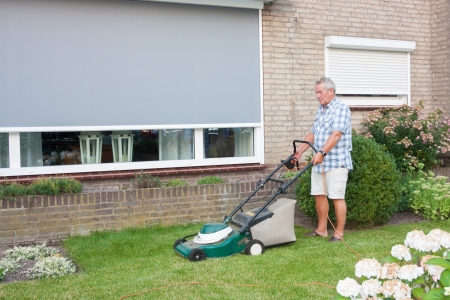 Dutch senior with serious look and mowing his front yard grass with an electric mower as spare time activity after retirement Stock Photo - 14731409