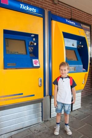 Glimlachend Little Nederlandse jongen op het station in de voorkant van een ticket machine wachten op de trein om terug te gaan naar school en het dragen van een rugzak