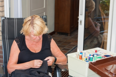 Close up of a Dutch senior retired woman stitching pants in her garden photo