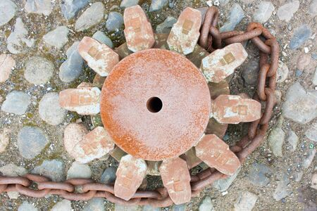 Very heavy and rusting dock chains and cog whee to real in and release or anchor a vessel to the bollards photo