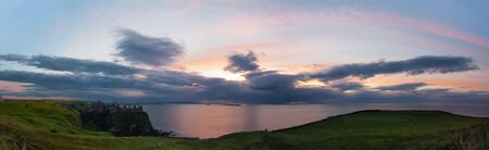 northern ireland: Panoramic view from Dunluce Castle of the atlanctic ocean and the sun setting over the Skerries Islands at Portrush
