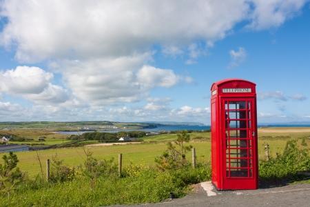 Rode telefooncel in Noord-Ierland met een achtergrond van kliffen en de Atlantische Oceaan en een klein dorpje schot in landschap Stockfoto