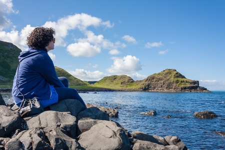 northern ireland: Young woman sitting on rocks relaxing and looking at the cliffs and atlantic ocean in northern ireland