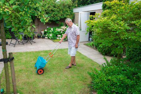 seeding: Dutch retired senior fertilising his grass lawn as retirement activity with a blue fertilizer dispenser on wheels