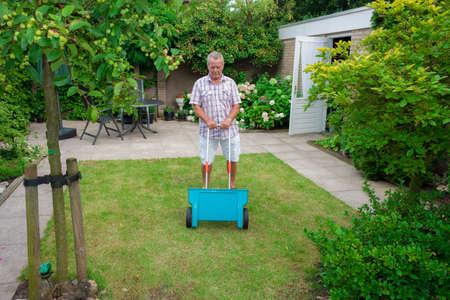 Dutch retired senior fertilising his grass lawn as retirement activity with a blue fertilizer dispenser on wheels photo
