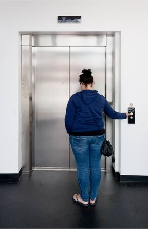 Young woman waiting in bright hallway and calling the elevator photo